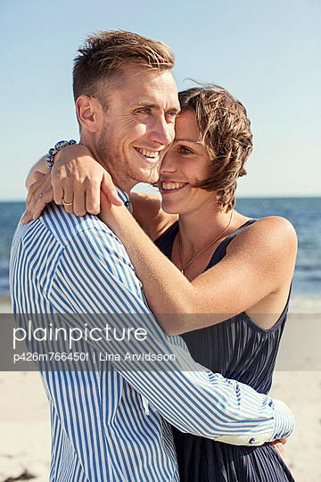 Happy couple embracing each other at beach