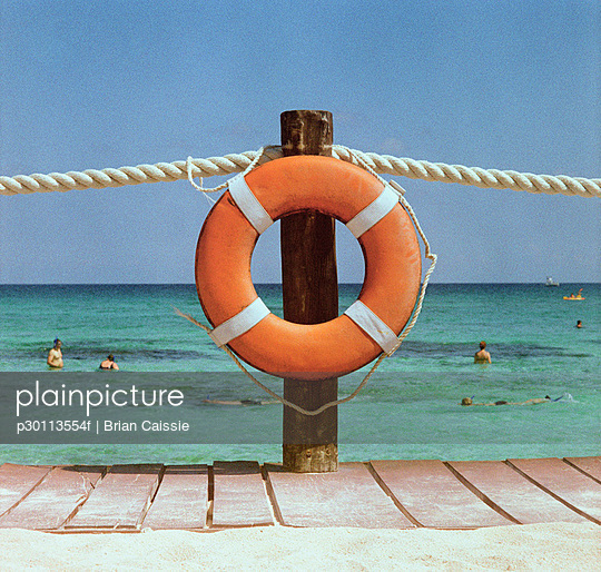 A life preserver hanging on a dock handrail and people swimming in the background