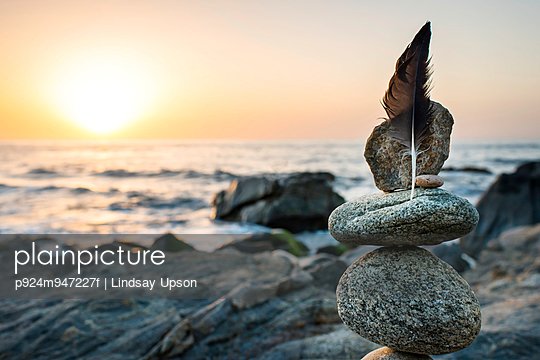 Still life of rocks and feather on beach
