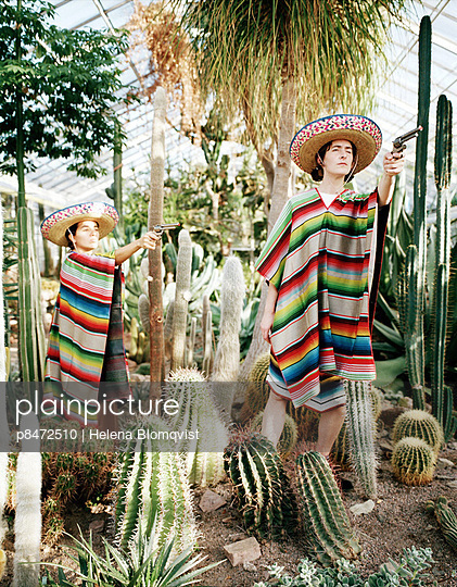 Two Persons In Mexican Clothes, Hat And Poncho Holding Revolver Among Catuses In Greenhouse