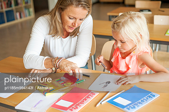 Teacher assisting girl in choosing color pencils during art class