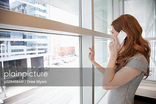 Woman talking on mobile phone and looking through window