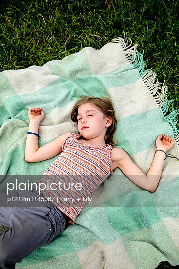 Mädchen schläft auf der Decke im Garten - p1212m1145987 von harry + lidy