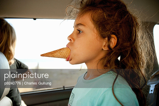 Young girl with ice cream cone in mouth