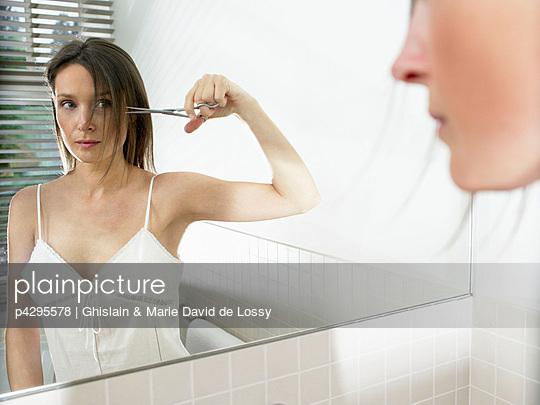 Woman in bathroom, cutting her hair