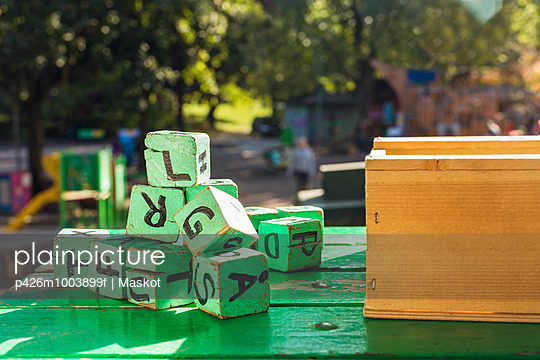 Green wooden blocks on table outside kindergarten