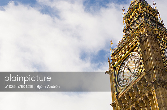 High section of clock tower of the Palace of Westminster against cloudy sky