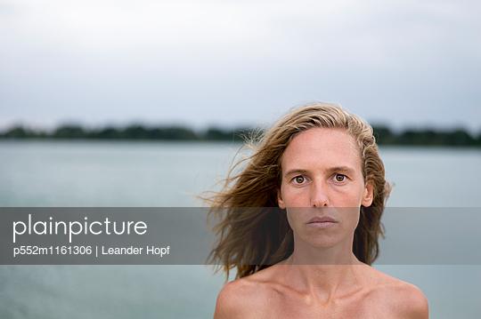 Porträt einer jungen Frau am See - p552m1161306 von Leander Hopf