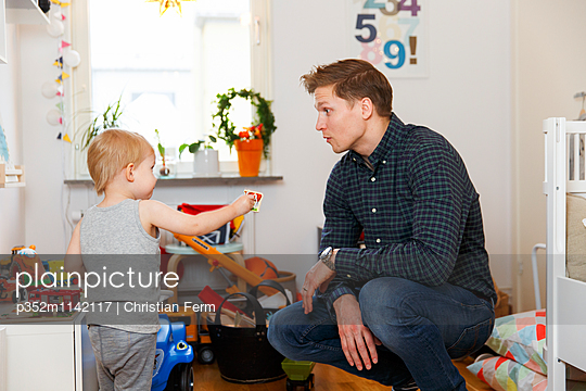 Sweden, Boy (2-3) showing toy to father