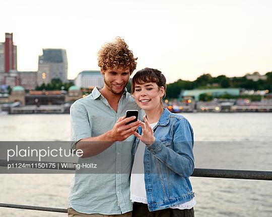 Paar mit Smartphone an der Elbe - p1124m1150175 von Willing-Holtz