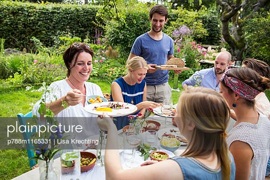 Gemeinsam essen auf einer Gartenparty - p788m1165331 von Lisa Krechting