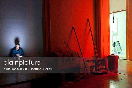 Frau sitzt auf Boden in einer leeren Wohnung, arbeitet am Laptop, Notebook, Computer, Parkett, Umzug, rotes Licht, Besen, Melancholie, MR, Leipzig, Sachsen, Deutschland - p1316m1160530 von Roetting+Pollex