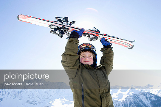 Boy holding skis above his head