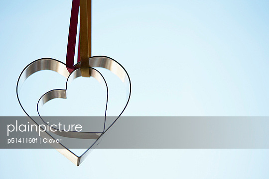 Two heart shaped cookie cutters hanging (close-up)