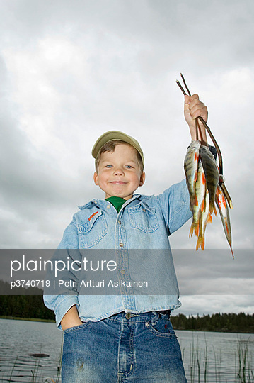 Portrait of a boy smiling and holding fish near a lake, Finland