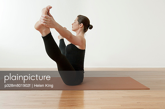 Young woman in yoga pose with legs apart