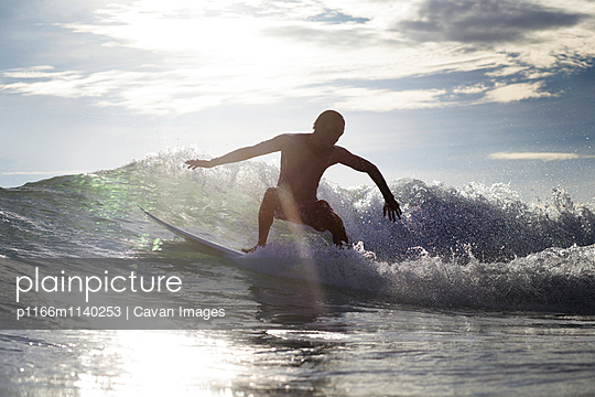Boy surfing on sea during summer vacation