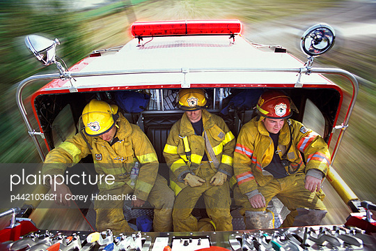 Firemen Riding On Back Of Fire Truck