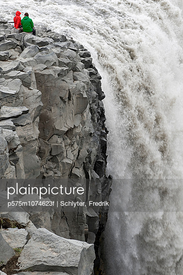 Couple sitting on rock and watching waterfall