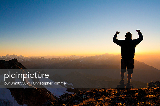A silhouetted hiker raises his hands in celebration after conquering the summit of Crystal Peak