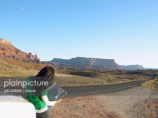 Woman reading map in desert, rear view, Moab, Utah, USA