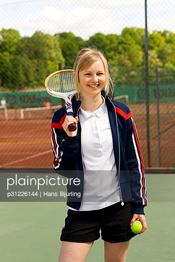 Young woman holding tennis racquet and ball, smiling, portrait