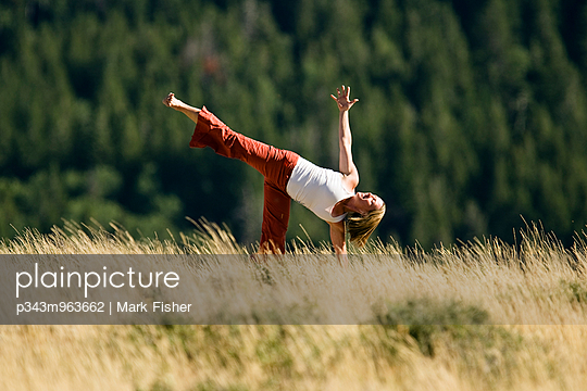 A young woman performs various yoga poses in view of the Tetons, Idaho