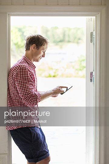 Profile shot of man using digital tablet at doorway