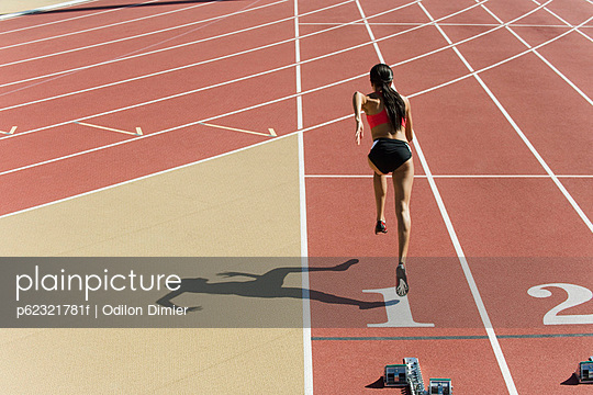 Woman running on track, rear view