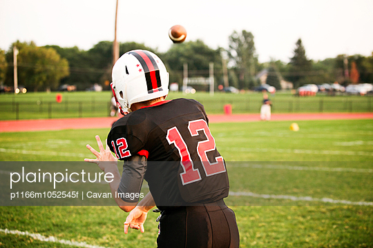 Teenage football player (14-15) throwing football