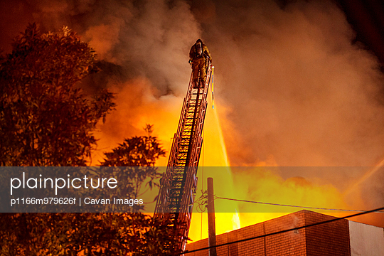 Fireman Fighting Fire From Top Of Ladder