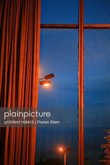 Vorhang an einem Fenster mit Blick auf Strassenlaternen bei Nacht, Kino International, Berlin, Deutschland, Europa - p1316m1160413 von Florian Stern
