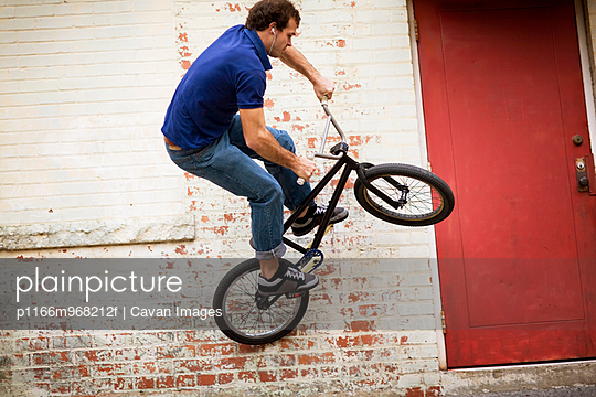 Bmx biker comitting to a wall plant