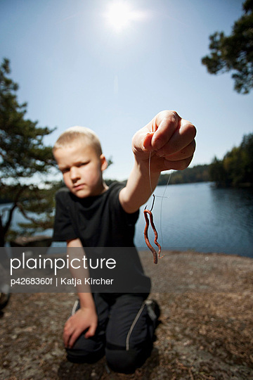 Young boy holding insect in his hand