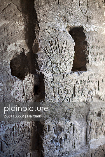 Handprints and handwritten graffiti etched into a stone wall