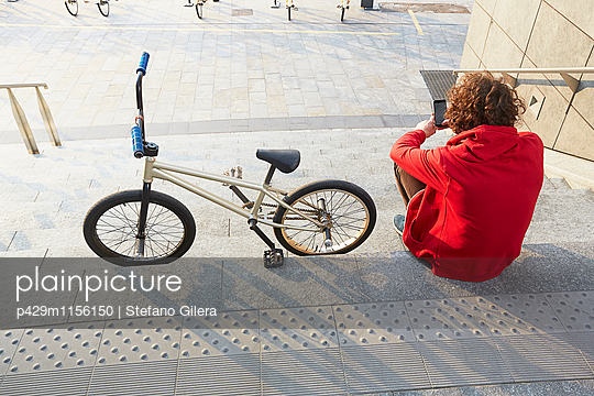 Rear view of man sitting on steps with BMX using smartphone