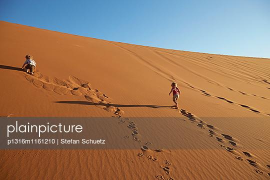 Zwei Jungen gehen Sanddüne hoch, Deadvlei, Sossusvlei, Namib-Naukluft-Nationalpark, Namibia - p1316m1161210 von Stefan Schuetz