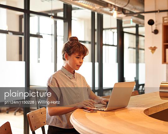 Junge Frau mit Laptop im Büro - p1124m1150228 von Willing-Holtz