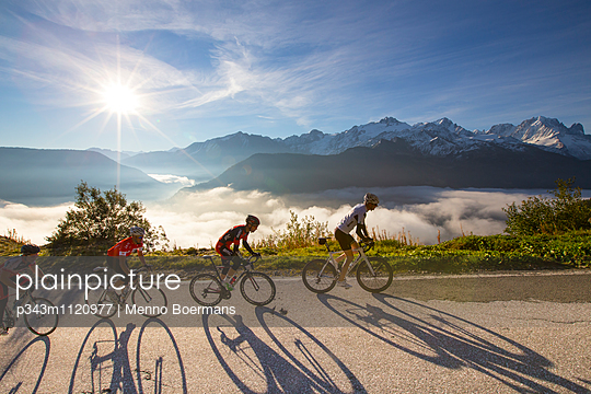Four road bikers on a winding mountain road on their way to the Emosson reservoir lake in the Alps on the border of France and Switzerland.