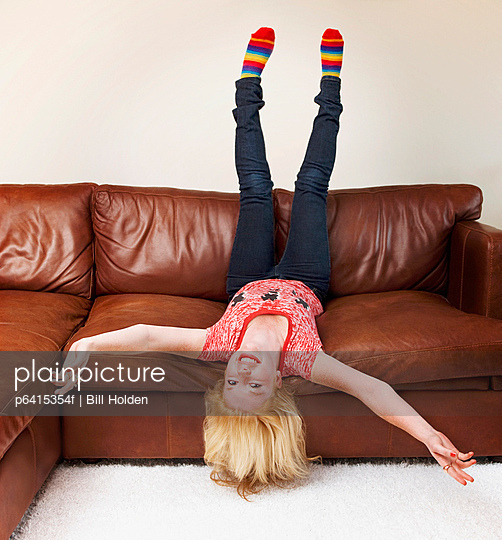 Teenage girl upside-down on sofa