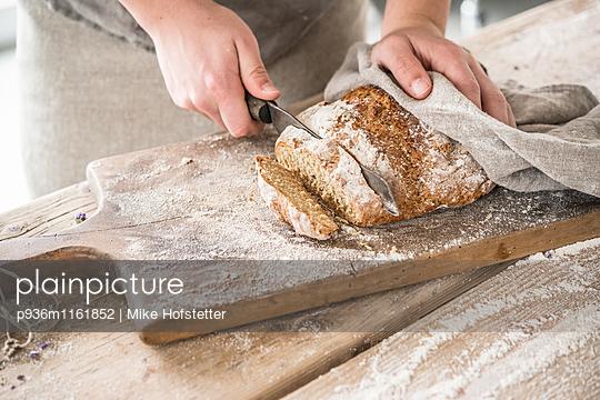 Frisches Brot anschneiden - p936m1161852 von Mike Hofstetter