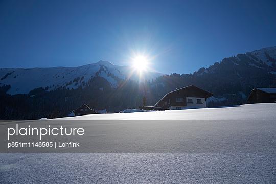 Ferienhäuser im Schnee bei Sonnenaufgang - p851m1148585 von Lohfink