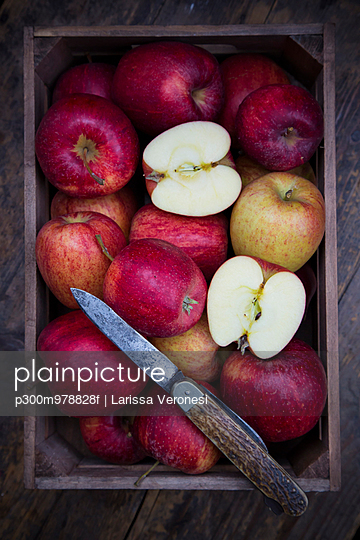 Wooden box of red apples and a pocket knife