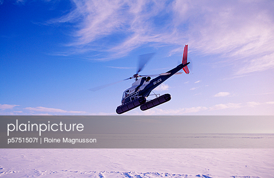 Helicopter flying over snow-covered land