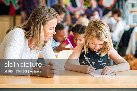 Mature teacher watching girl studying in classroom