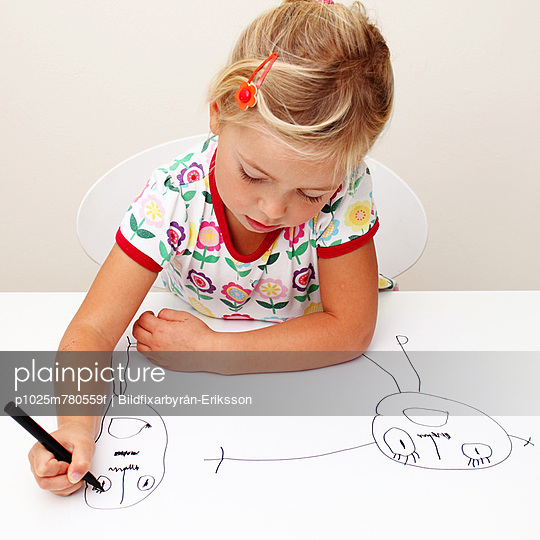 Little girl drawing cephalopods against plain background