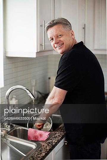 Portrait of mature man washing utensil in kitchen