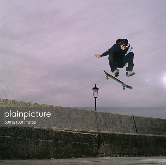 Man jumping in air with skateboard