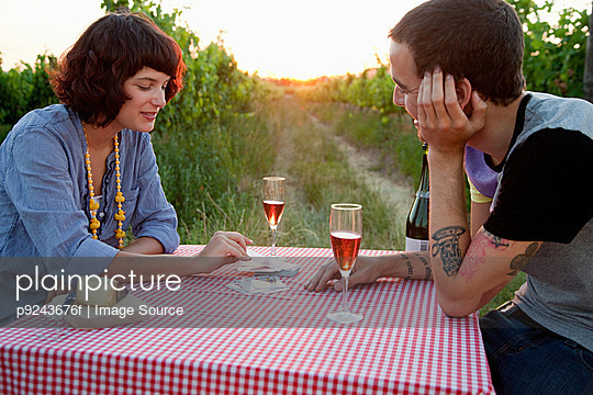 Couple playing cards on table in field