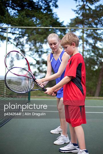 Female tennis player coaching pre-teen boy